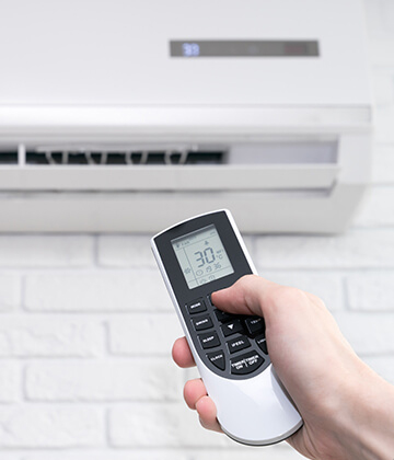 Optimal temperature of air in the room shown on display of remote in human hand