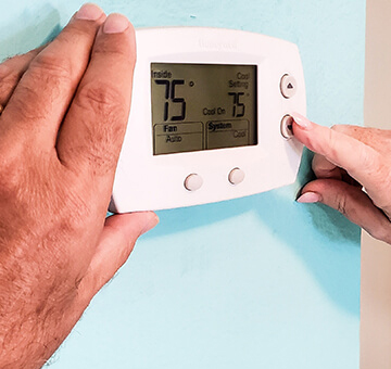 Hand turning a home thermostat knob to set temperature on energy saving mode
